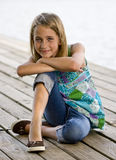 Young tween girl kneeling on a dock. Royalty Free Stock Photos