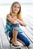 Young tween girl kneeling on a dock. Stock Image
