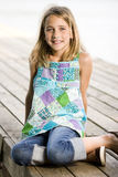 Young tween girl sitting on a pier. A young, pretty, preadolescent girl  sitting on a dock and smiling at the camera Royalty Free Stock Photos
