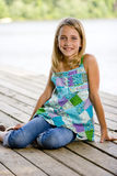 Young tween girl sitting on a pier. A young, pretty, preadolescent girl sitting on a dock and smiling at the camera Royalty Free Stock Image