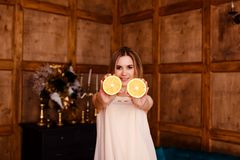 Young twenty year old smiling woman shows two halves of orange. Indoors royalty free stock images