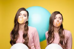 Young twins holding pink and white balloons in their hands. Young twins in elegant dresses holding pink and white balloons in their hands. Brunette sisters with stock photography