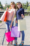 Young twins girls have fun holding their shopping bags Royalty Free Stock Photography