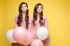 Young twins holding pink and white balloons in their hands. Young twins in elegant dresses holding pink and white balloons in their hands. Brunette sisters with royalty free stock photo
