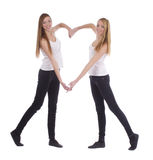 Young twins sisters making heart shape with arms. On white Stock Images