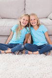 Young twins sitting on a carpet Stock Image