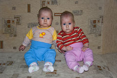 Young twins sitting on couch Stock Photo