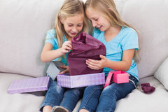 Young twins unwrapping birthday gift sitting on a couch. In the living room Stock Photo