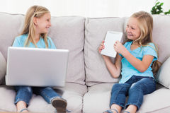 Young twins using a laptop and a tablet sitting on a couch Royalty Free Stock Photo