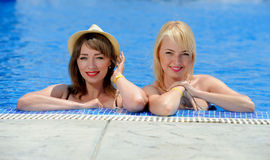 Young two girls in a bikini at the pool Stock Images