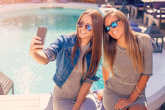 Young two girls laughing and taking selfie Stock Photos