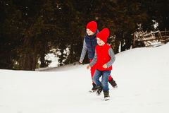 Young two happy kids playing outdoors in winter park Royalty Free Stock Images
