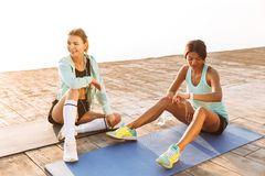 Young two sports women friends outdoors on the beach sitting talking with each other royalty free stock photo