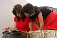 Young two women in reading magazine Stock Photos