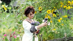Young Ukrainian doing selfie on the nature. On her neck is a necklace of beads - gerdan, on her wrist a bracelet with red beads, in her hands bouquet of stock video