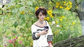 Young ukrainian doing selfie on the nature. On her neck is a necklace of beads - gerdan, on her wrist a bracelet with red beads, in her hands bouquet of stock video footage