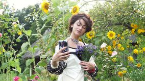 Young ukrainian doing selfie on the nature. On her neck is a necklace of beads - gerdan, on her wrist a bracelet with red beads, in her hands bouquet of stock footage