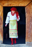 Young ukrainian girl, dressed in national costume, walking out from house Royalty Free Stock Image