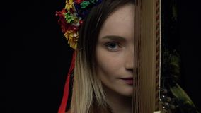 Ukrainian girl playfully looks at the camera near the pandora. Young Ukrainian girl is fascinated looking forward holding in bandura hands stock video footage