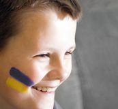Young Ukrainian team fan. A boy with the painted face, the Ukrainian traditional flag colours. A smile on his face Stock Photos