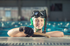 Young underwater hockey player. Beautiful young girl at swimming pool. Underwater hockey player royalty free stock image