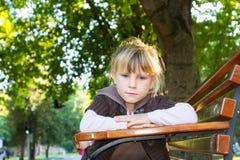 Young unhappy child girl in autumn park. Outdoor portrait of young unhappy child girl in autumn park Stock Photos