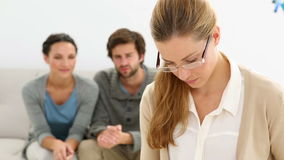 Young unhappy couple sitting on sofa behind therapist. At therapy session stock video footage