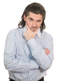 Young unhappy man with hand at chin speculates. Young worried dark haired businessman in light blue striped shirt holds hand on his chin isolated on white Royalty Free Stock Photography