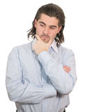 Young unhappy man holds hand at chin and thinks. Young worried dark haired businessman in light blue striped shirt holds hand on his chin isolated on white Royalty Free Stock Photography