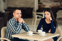Young unhappy married couple having serious quarrel at cafe Stock Images