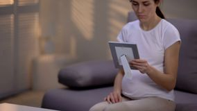 Young unhappy pregnant widow looking at photo in frame, suffering loneliness royalty free stock photos