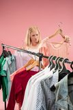 The young unhappy pretty girl looking at dresses and try on it while choosing at shop. Image of pretty unhappy female looking a dress while choosing it. Concept stock photos