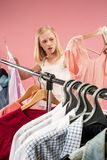 The young unhappy pretty girl looking at dresses and try on it while choosing at shop. Image of pretty unhappy female looking a dress while choosing it. Concept royalty free stock photography