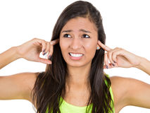 Young unhappy, stressed woman covering her ears looking away, as if to say, stop making that loud noise it's giving me a headache Stock Photography