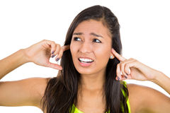 Young unhappy, stressed woman covering her ears looking away, as if to say, stop making that loud noise it's giving me a headache Royalty Free Stock Photos