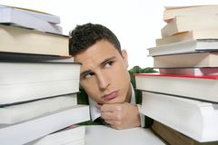 Young unhappy student with stacked books Stock Photo
