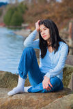 Young unhappy teen girl sitting on rocks along lake shore, looking off to side, head in hand. Young unhappy biracial teen girl in blue shirt and jeans sitting on Stock Photos