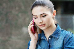 Young unhappy teen woman. Closeup portrait young unhappy teen woman, talking on cell phone having unpleasant, bad conversation, outdoor. Negative emotions Royalty Free Stock Image