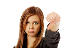 Young unhappy teenage woman showing thumb down Royalty Free Stock Images