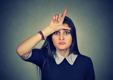 Young unhappy woman giving loser sign on forehead. Closeup portrait young unhappy woman giving loser sign on forehead, looking at you, disgust on face  on gray Royalty Free Stock Images