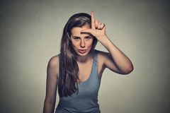 Young unhappy woman giving loser sign on forehead. Closeup portrait young unhappy woman giving loser sign on forehead, looking at you, disgust on face isolated Stock Photography