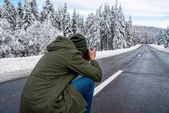 Young unidentifiable photographer taking outdoor images. On slippery asphalt road at wintertime royalty free stock photography