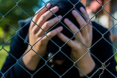 Young unidentifiable teenage boy holding hes head at the correctional institute ,conceptual image of juvenile delinquency. Focus on the wired fence royalty free stock photo