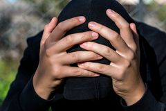 Young unidentifiable teenage boy holding hes head at the correctional institute. Conceptual image of juvenile delinquency, focus on the boys hand royalty free stock image