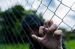 Young unidentifiable teenage boy holding the wired garden at the correctional institute. Conceptual image of juvenile delinquency, focus on the boys hand royalty free stock images
