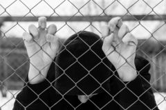 Young unidentifiable teenage boy holding the wired garden at the correctional institute. Conceptual image of juvenile delinquency, focus on the boys hands stock images