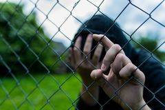Young unidentifiable teenage boy holding the wired garden at the correctional institute. Covering hes face , conceptual image of juvenile delinquency, focus stock photo