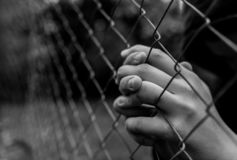 Young unidentifiable teenage boy holding the wired garden  praying at the correctional institute. In black and white, conceptual image of juvenile delinquency royalty free stock photo