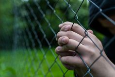 Young unidentifiable teenage boy holding the wired garden  praying at the correctional institute. Conceptual image of juvenile delinquency, focus on the boys stock photography