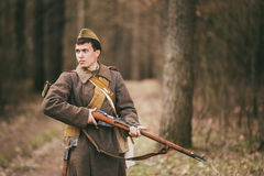 Young unidentified re-enactor dressed as Soviet soldier gunner goes along a forest road. Stock Photos